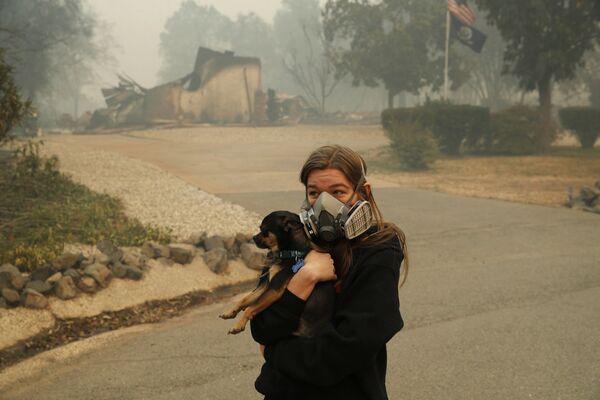 Девушка с собакой возле сгоревшего дома в Калифорнии, США