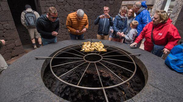 Туристы в ресторане «El Diabolo», в котором еду готовят над кратером вулкана, Лансароте, Испания