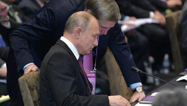 Президент России Владимир Путин  и помощник президента Юрий Ушаков на пленарном заседании Восточноазиатского саммита в Сингапуре. 15 ноября 2018