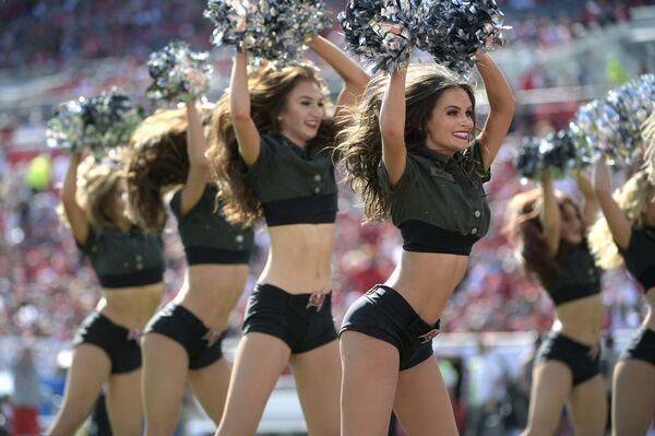 Выступление черлидинговой команды во время матча по американскому футболу в Тампе, штат Флорида, США
