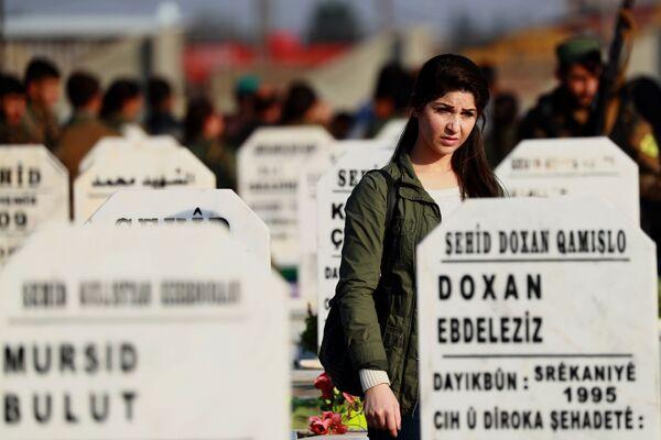 Боец Демократических сил Сирии на похоронах убитого во время военных действий в Эль-Камышлы солдата