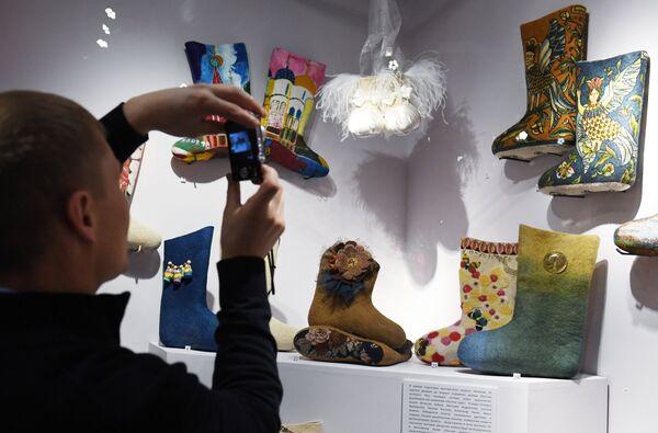 Посетитель фотографирует дизайнерские валенки на выставке Валенки. От царских дворцов до модных подиумов