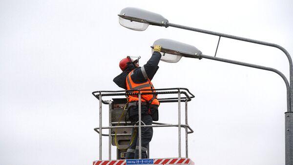 Рабочий меняет лампы в уличных фонарях. Архивное фото