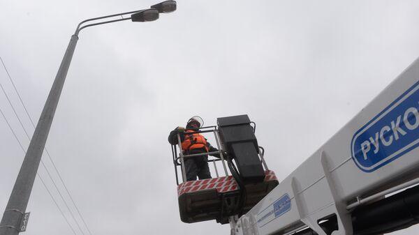 Сотрудник ОЭК работает с уличным фонарем