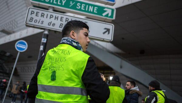 Участник акции протеста против роста цен на бензин желтые жилеты в Париже. 24 ноября 2018