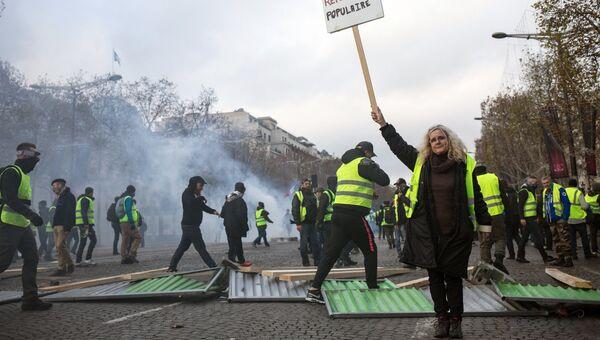 Участники акции протеста против роста цен на бензин желтые жилеты в Париже. 24 ноября 2018