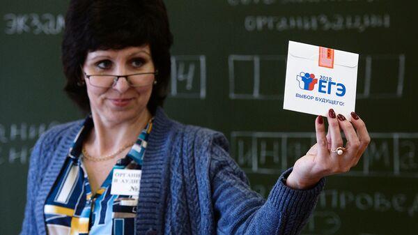 Учитель демонстрирует конверт с диском, на котором содержатся задания для ЕГЭ по информатике. Архивное фото