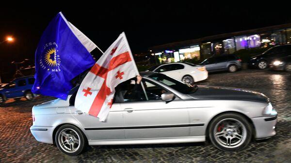 Автомобиль с флагом правящей партии Грузинская мечта и Государственным флагом во время празднования итогов окончания голосования во втором туре президентских выборов в Грузии