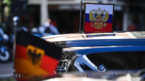 Штандарт президента РФ на автомобиле президентского кортежа и флаг Германии на автомобиле кортежа канцлера ФРГ