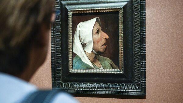 Посетительница рассматривает картину Питера Брейгеля-старшего Старая крестьянка на выставке в Художественно-историческом музее Вены