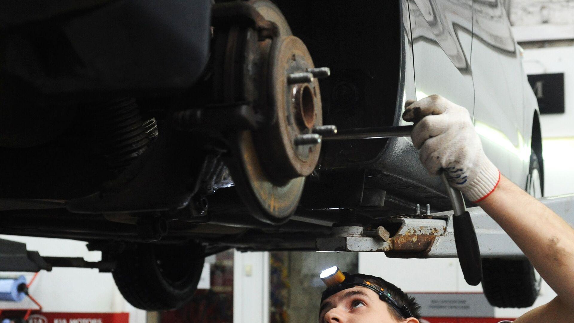 Сотрудник проводит техническое обслуживание автомобиля - РИА Новости, 1920, 09.10.2020