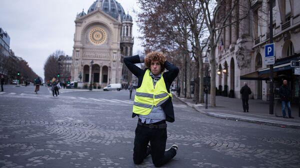 Участник акции протеста движения автомобилистов желтые жилеты в районе Триумфальной арки в Париже