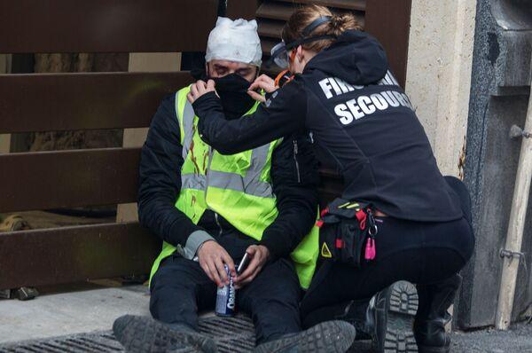 Участник акции протеста движения автомобилистов желтые жилеты в районе Триумфальной арки в Париже получает медицинскую помощь