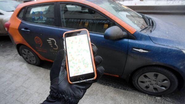 Пользователь каршеринга просматривает через приложение на смартфоне доступные автомобили