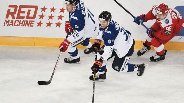 Хоккеисты сборной Финляндии Ере Саллинен, Анрей Хакулинен и нападающий сборной России Андрей Кузьменко (слева направо)