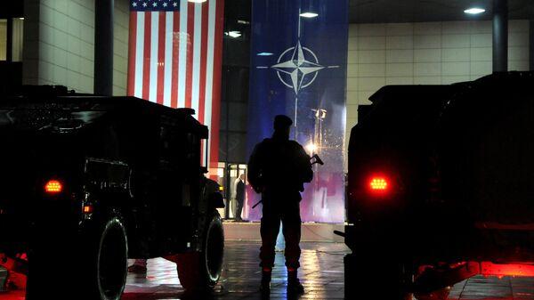 Военнослужащий сил безопасности Косово стоит перед флагами США и НАТО в Приштине