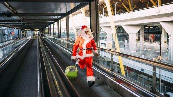 Мужчина в костюме Деда Мороза бежит с чемоданом в аэропорту