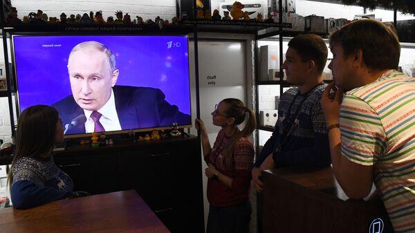 Люди смотрят прямую трансляцию ежегодной большой пресс-конференции президента РФ Владимира Путина в магазине во Владивостоке