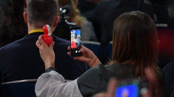 Журналистка фотографирует неваляшку во время ежегодной большой пресс-конференции президента РФ Владимира Путина