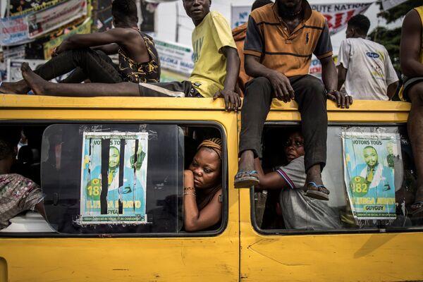 Пассажиры наблюдают за демонстрацией сторонников оппозиции в Киншасе
