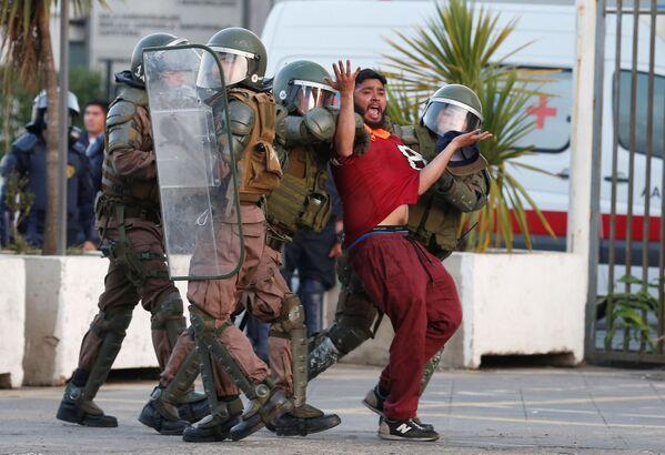 Портовый грузчик, задержанный в ходе акции протеста против оператора TPS  в Вальпараисо, Чили