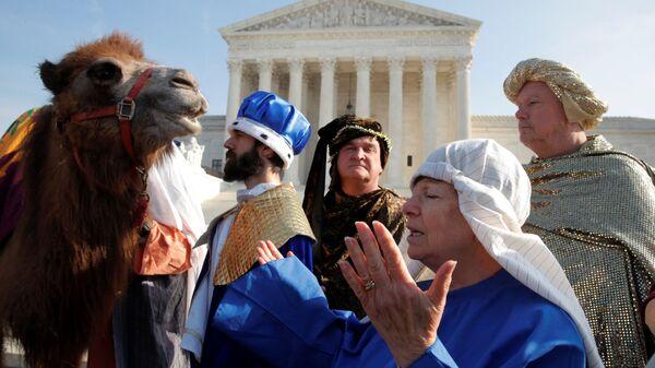 Женщина совершает молитву рядом с актерами, одетыми как Три волхва в Вашингтоне, США