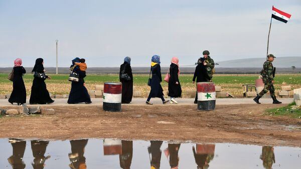 Сирийские беженцы пересекают гуманитарный коридор Абу-Духур в окрестностях провинции Идлиб