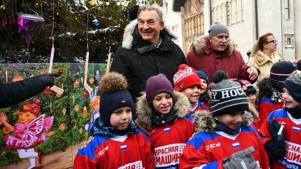 Президент Федерации хоккея России Владислав Третьяк и дети из школы олимпийского резерва по хоккею, принявшие участие в украшении новогодней елки на Соборной площади Московского Кремля
