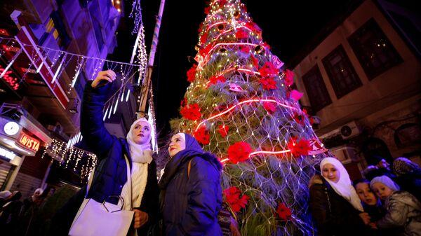 Жители возле рождественской елки в Дамаске