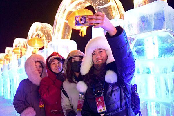 Гости фестиваля фотографируются на фоне ледяных скульптур в городе Маньчжурия