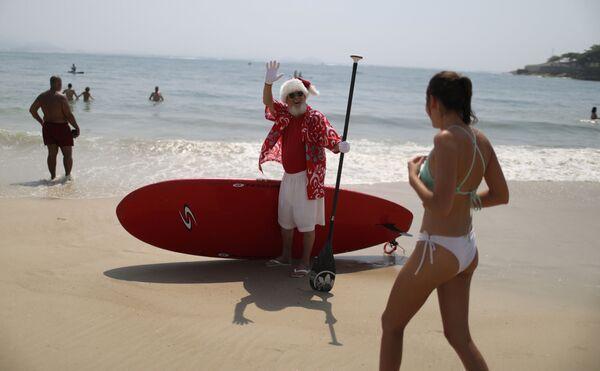 Мужчина в костюме Санта-Клауса приветствует людей на пляже Копакабана в Рио-де-Жанейро, Бразилия