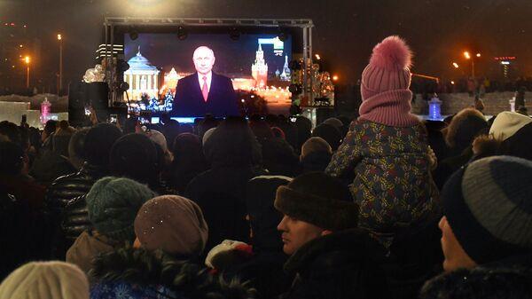 Горожане слушают обращение президента РФ Владимира Путина во время встречи Нового года — 2019 у Центральной елки в Казани
