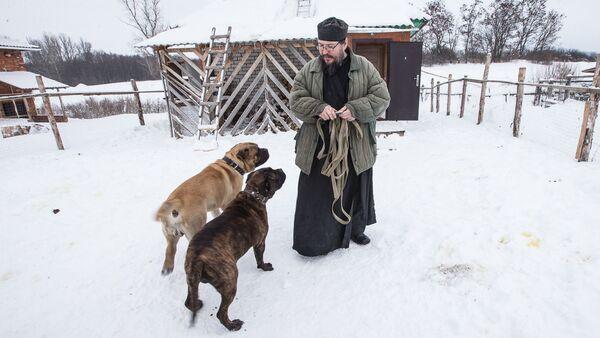 Игумен Агафангел (Белых) с собаками Клепой и Персиком на территории монастырского скита в селе Новотроевке Белгородской области