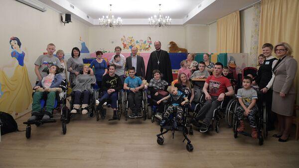 Президент РФ Владимир Путин и протоиерей Александр Ткаченко фотографируются с пациентами Детского хосписа в Санкт-Петербурге. 6 января 2019