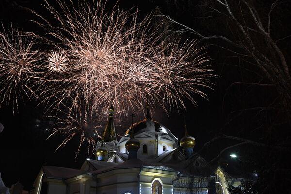 Праздничный фейерверк возле Вознесенского кафедрального собора в Новосибирске в честь Рождества Христова. 6 января 2019