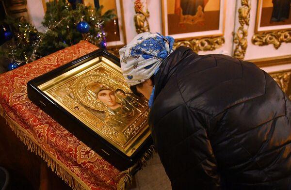 Женщина склоняется перед иконой Богоматери во время рождественского богослужения в храме святого апостола Андрея Первозванного во Владивостоке. 6 января 2019