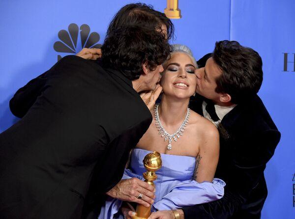 Энтони Россомандо, Эндрю Уайетт и Марк Ронсон целуют Леди Гагу на премии Золотой глобус в Беверли-Хиллз. 6 января 2019