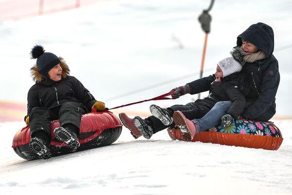 Посетители катаются на тюбингах с горки горнолыжного курорта Лисья Гора в Московской области