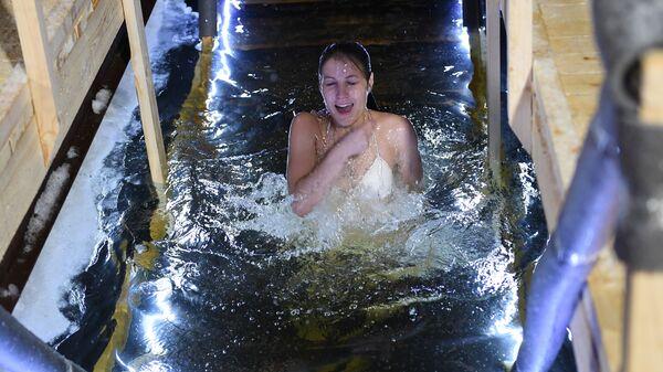 Девушка во время традиционных купаний в праздник Крещения на берегу Москвы-реки возле ЖК Алые паруса