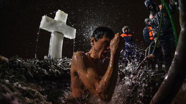Мужчина во время традиционных купаний в праздник Крещения у храма Живоначальной Троицы в поселке Норское