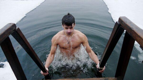 Мужчина во время крещенских купаний в проруби в Донецке. 19 января 2019