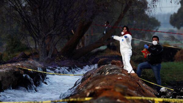 Судмедэксперты работают на месте взрыва топливопровода, предположительно взломанного ворами, в муниципалитете Тлауэлилпан в Мексике. 19 января 2019