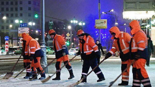 Сотрудники коммунальных служб убирают снег на улице Москвы