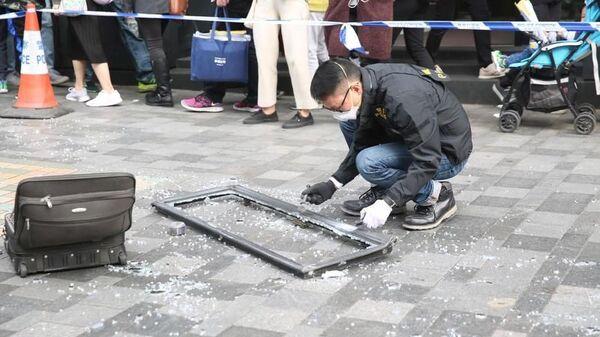 Сотрудник полиции Гонконга осматривает оконную раму, которая упала на туристку и убила ее