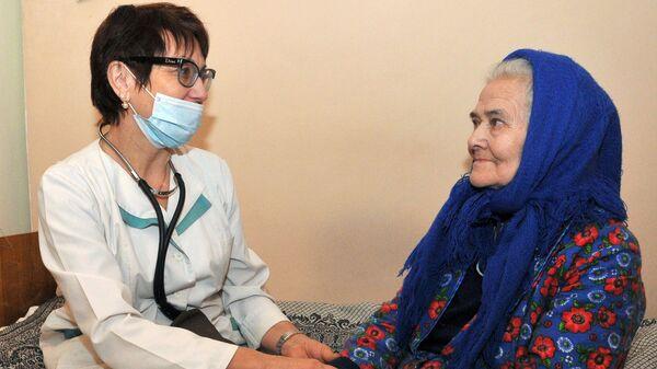 Медицинский работник Центра по оказанию социальной помощи лицам без определенного места жительства осматривает пациентку