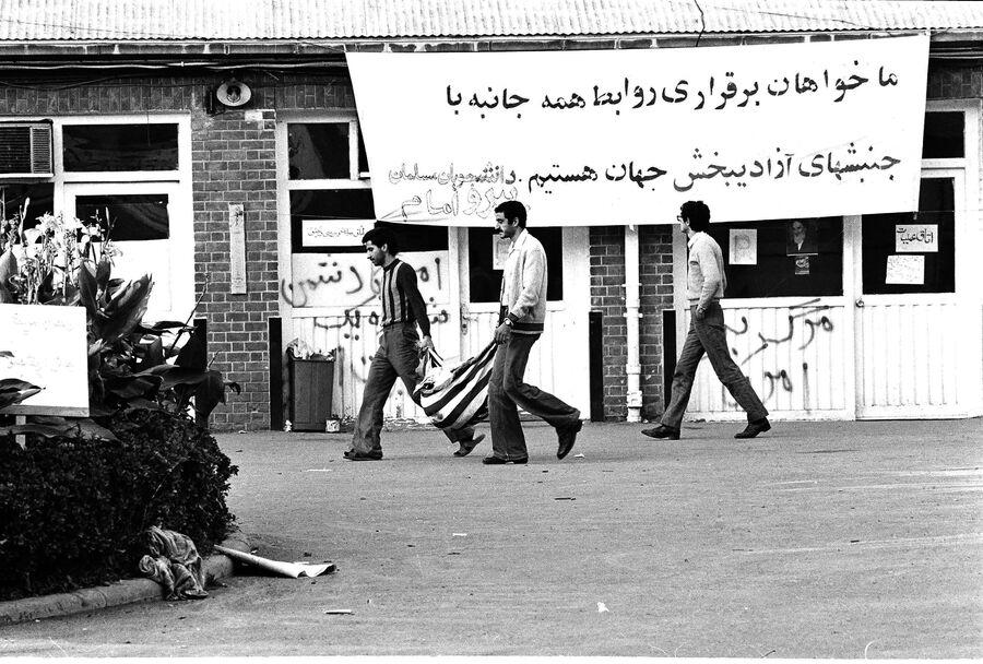 Иранцы выносят мусор на национальном флаге США из посольства в Тегеране. 13 ноября 1979
