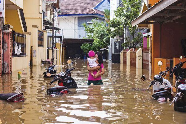 Женщина несет свою дочь во время наводнения в Макассаре, Индонезия