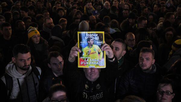 Журнал в руках болельщика с изображением пропавшего без вести Эмилиано Салы