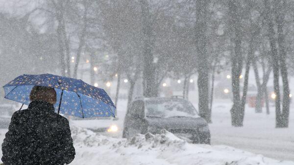 Прохожая во время снегопада на Ленинском проспекте в Москве