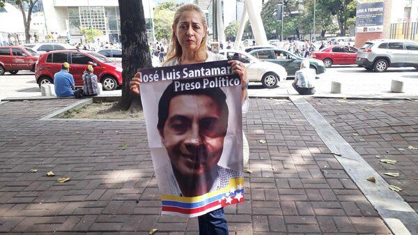 Участница митинга оппозиции в Каракасе держит плакат с изображением Хосе Луиса Сантамарии, арестованного после уличной демонстрации 2014 года